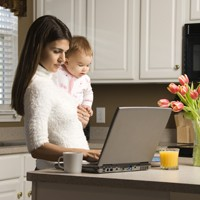 Picture of mother working on her computer while holding her child