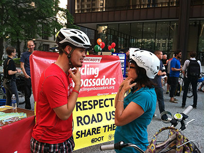 A Bicycling Ambassador properly fits a cyclist's helmet at the annual Chicago Bike to Work Rally.