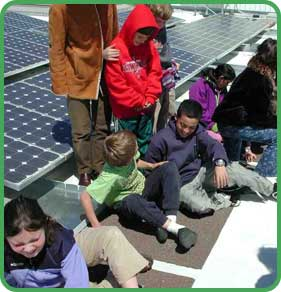 Students sitting next to solar panels
