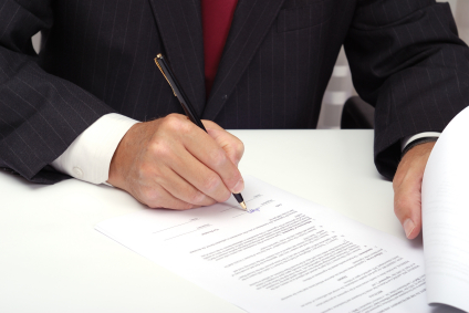 Image of man signing document