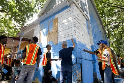 Mayor Rahm Emanuel lends a brush to the efforts of youth from the One Summer Chicago PLUS program to beautify parts of Englewood by painting over dilapidated houses in August 2015.