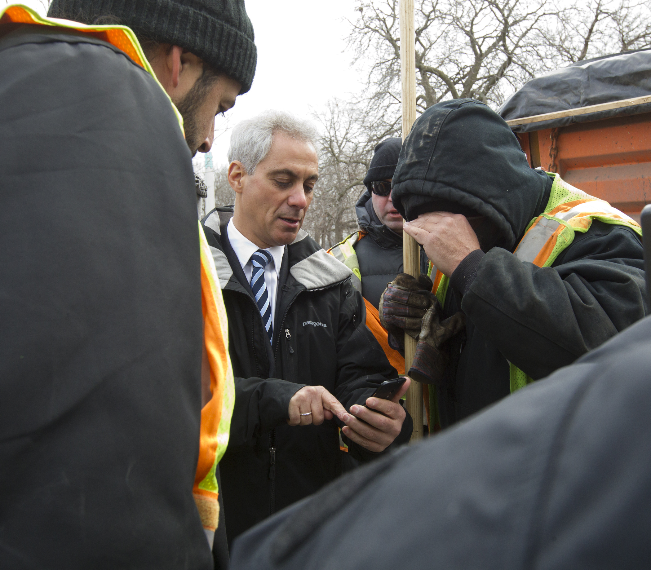 Mayor Rahm Emanuel uses his smartphone to demonstrate the new Pothole Tracker during a stop to thank CDOT crews filling potholes on North Marine Drive.