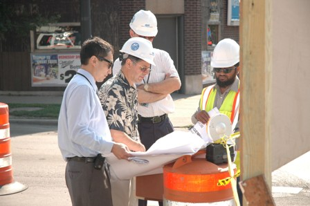 Engineers on the street reviewing sewer plans