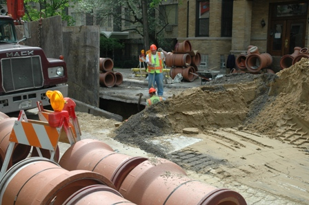 Street view of a Department of Water Management crew and equipment in the process of installing a new sewer main.
