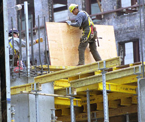 A construction worker holding a wooden board