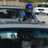 Man on a motorcycle and some cars in traffic