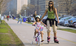 Mother skating with her young daughter riding a bike on the sidewalk