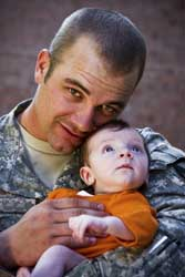 A man in uniform holding a baby