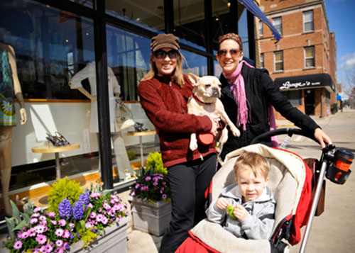Two women, one holding a dog and the other a stroller with a child