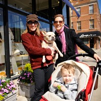 Two women one holding a dog and the other holding a stroller with child