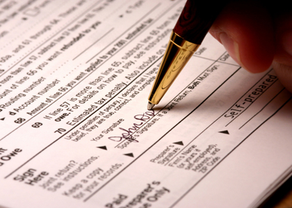 Photo of someone filling out a tax form