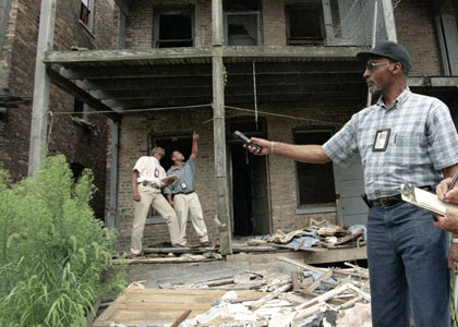 Three inspectors outside a dilapidated building