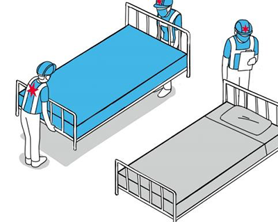 three people setting up hospital beds
